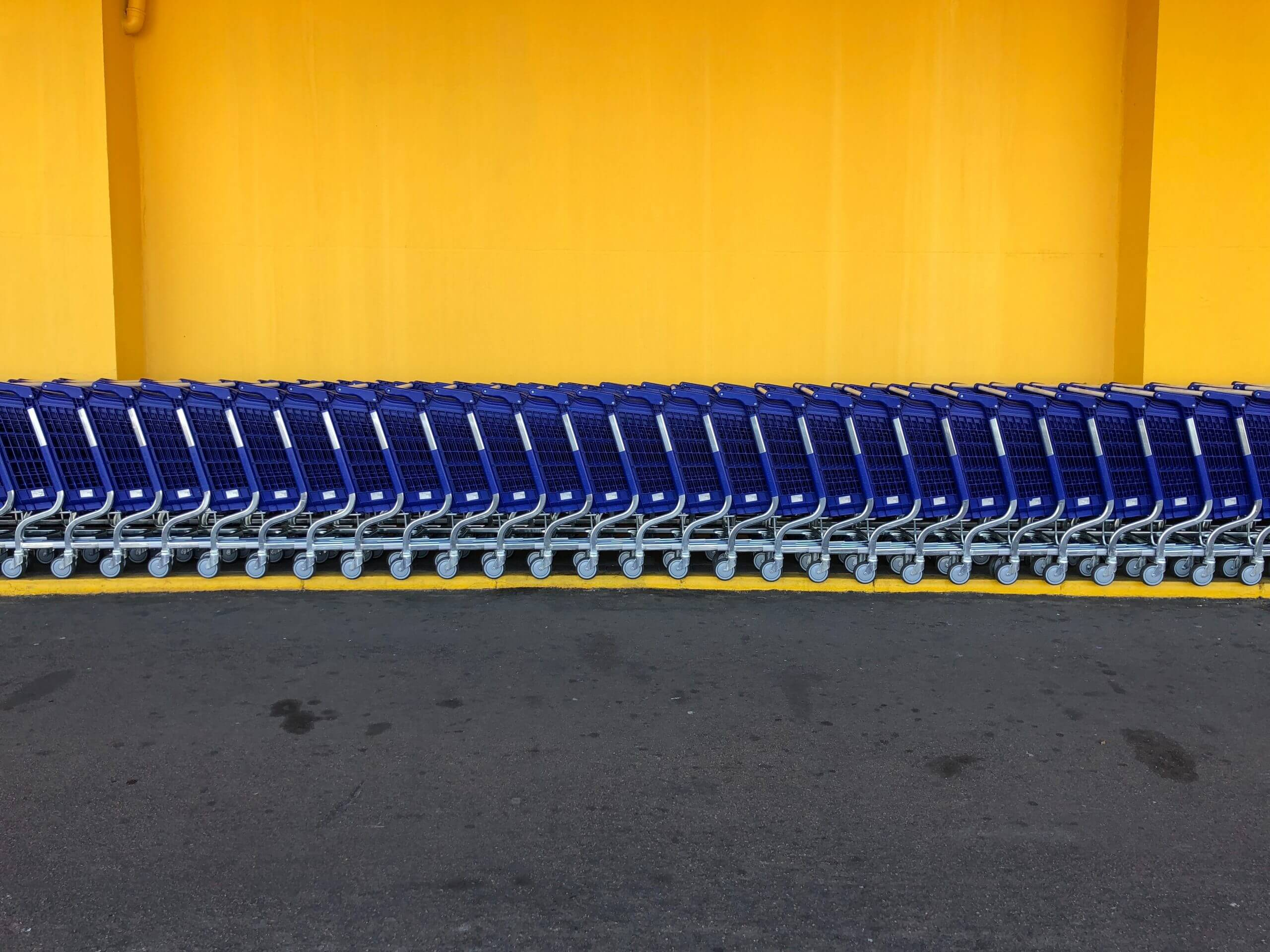Arranged blue shooping carts in front of yellow wall