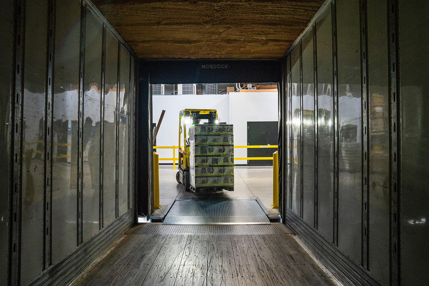 Yellow Forklift driving pallet into truck
